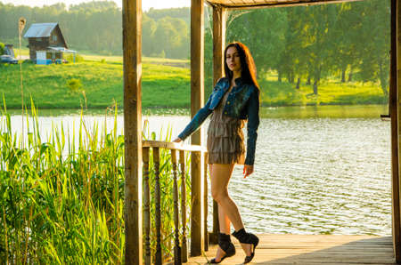 tiptoes: girl standing on a wooden pier . brunette in a short summer dress is standing on tiptoes on the pier at the pond. Stock Photo