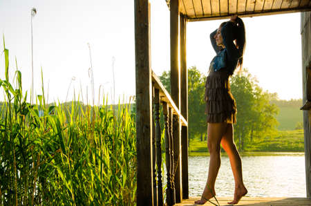 long toes: girl standing on a wooden pier . barefoot brunette in a short summer dress is standing on tiptoes on the pier at the pond. Stock Photo