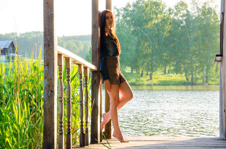 tiptoes: girl standing on a wooden pier . barefoot brunette in a short summer dress is standing on tiptoes on the pier at the pond. Stock Photo