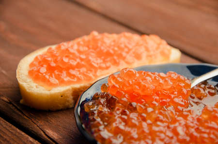 red caviar in a blue plate. wood planks. Sandwich with butter and caviar Stock Photo