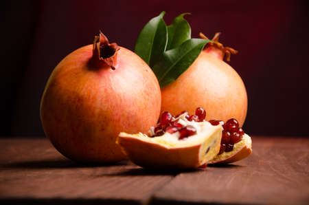 old desk: juicy pomegranate on wooden boards.cut into pieces of ripe pomegranate. the pomegranate is ripe. ripe pomegranate seeds. fresh juicy leaves