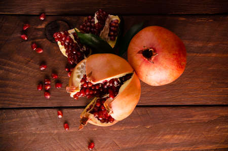 juicy pomegranate on wooden boards.cut into pieces of ripe pomegranate. the pomegranate is ripe. ripe pomegranate seeds. fresh juicy leaves