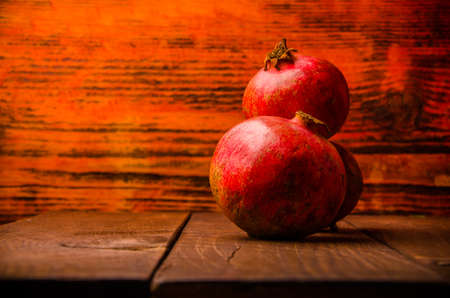 ripe pomegranate on wooden boards. juicy pomegranate on wooden boards. Foto de archivo