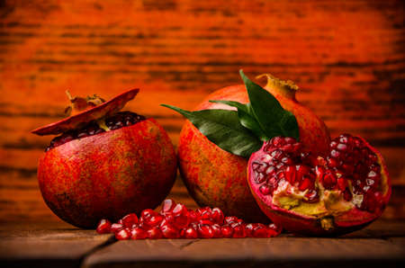 ripe pomegranate seeds. fresh juicy leaves. juicy pomegranate on wooden boards.cut into pieces of ripe pomegranate. the pomegranate is ripe.