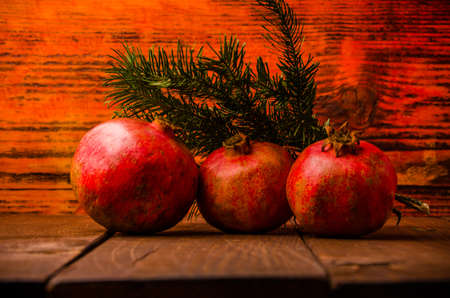 juicy pomegranate on wooden boards. fresh green fir branch. ripe pomegranate on wooden boards. Stock Photo