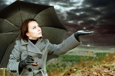 lluvia paraguas: Mujer joven con un paraguas negro. Foto de archivo