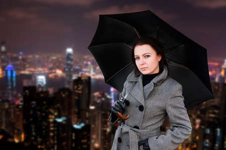 umbrella rain: Woman with umbrella in night city. Stock Photo