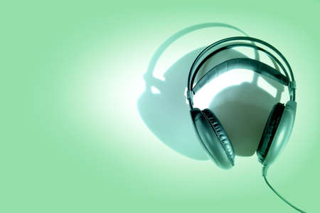 aural: headphones with shadow on green background Stock Photo