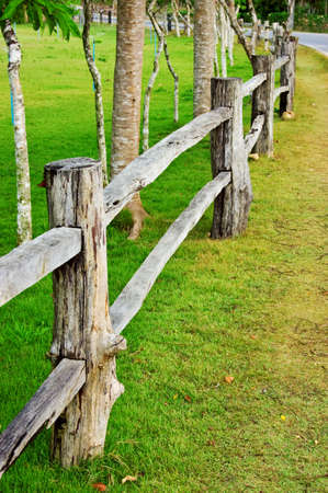 Wooden fence on green field photo