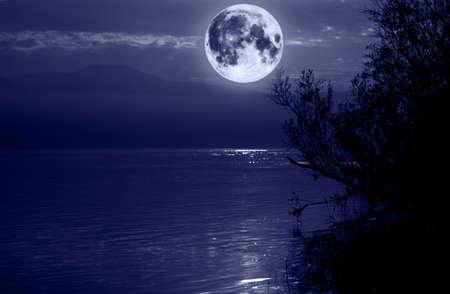 luz de luna: Big blue moon sobre el agua Foto de archivo