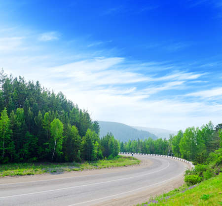 winding road: Mountain road and blue sky. Stock Photo