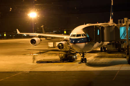 airport runway: commercial airplane loading. night scene. Stock Photo