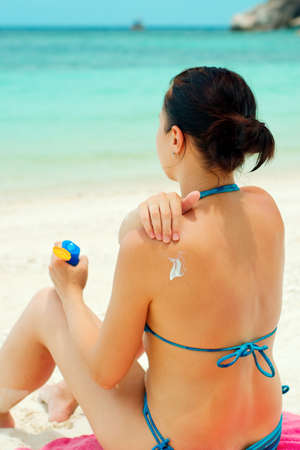 sun lotion: Woman applying sun lotion on the beach. Stock Photo
