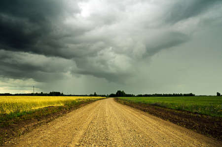 single lane road: Stormy sky over the ground road.