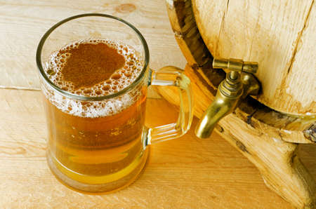 mug of ale: Beer and barrel on the wood table. Stock Photo