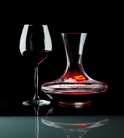 Decanting of red wine. Black background. photo