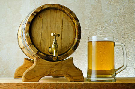 booze: Beer and barrel on the wood table. Stock Photo