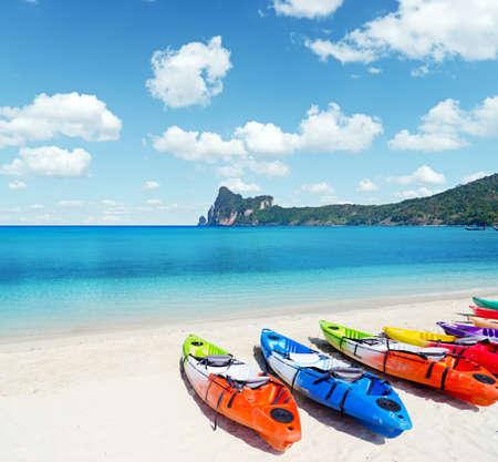 adventure travel: Colourful kayaks on tropical beach. Stock Photo