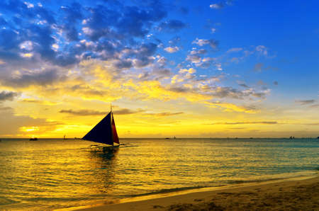 boating: Sunset  landscape. Sailboat on coast of Boracay island. Stock Photo