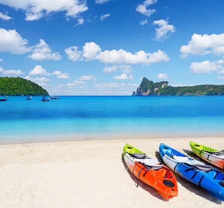 Colourful kayaks on tropical beach. photo