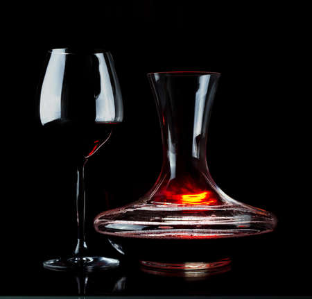 carafe: Decanting of red wine. Black background. Stock Photo