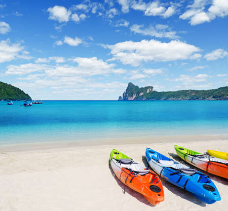 adventure holiday: Colourful kayaks on tropical beach. Stock Photo