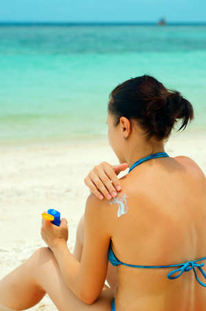 sun lotion: Woman applying sun lotion on the beach  Stock Photo