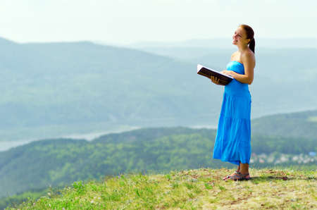 Red haired woman with book on the hilltop. Stock Photo - 14022505