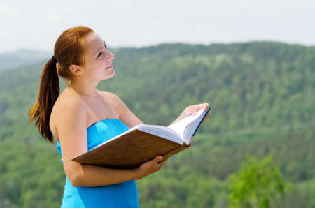 Red haired woman with book on the hilltop. Stock Photo - 14023017