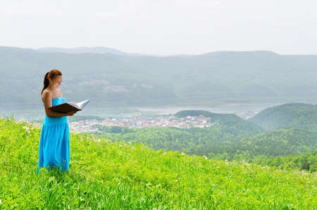 Red haired woman with book on the hilltop. photo
