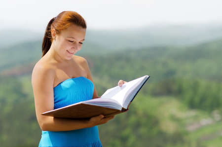 red haired: Red haired woman with book on the hilltop. Stock Photo