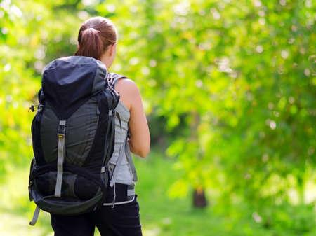 camp de vacances: Jeune femme avec sac � dos dans un bois. Randonn�e � l'�t�.