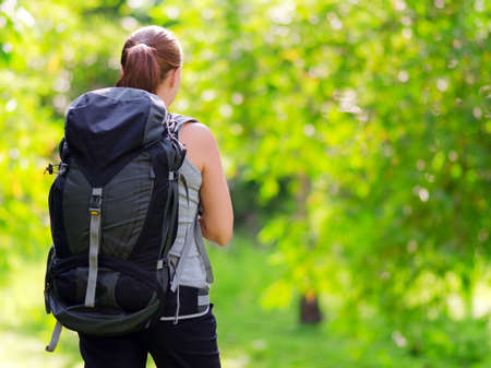 mochila de viaje: Mujer joven con mochila en un bosque. Senderismo en verano. Foto de archivo
