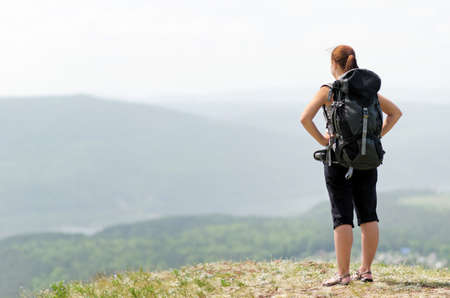 backpacking: Woman with backpack on green hill.
