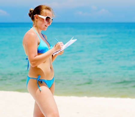 Young woman with notebook on a beach  photo