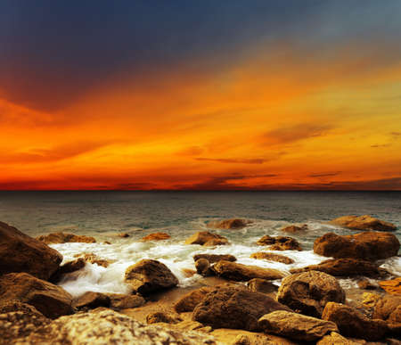 Red sky over a rocky seashore  Sunset landscape  photo