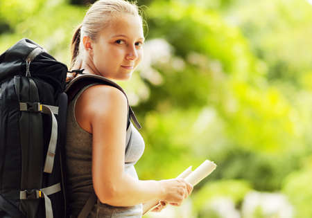 Young woman with backpack in a woods  Hiking at summertime  photo