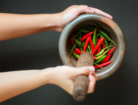 Red and green pepper in mortar. photo