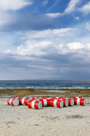 Lot of oil barrels on a seashore. Environment pollution. photo