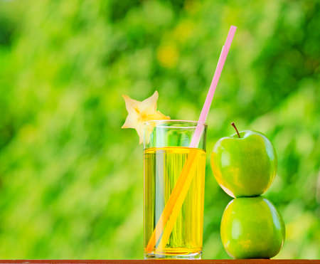 Glass of apple juice in a garden. photo