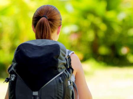 バックパック: 森のバックパックを持つ若い女性。夏にハイキング。