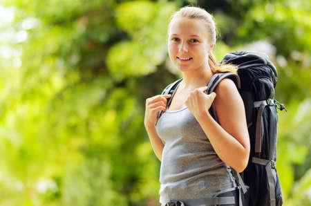 Jeune femme avec sac à dos dans un bois. Randonnée à l'été.