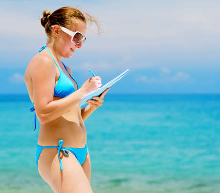Young woman with notebook on a beach. photo