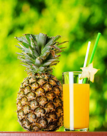 pineapple  glass: Glass of pineapple juice in a garden.