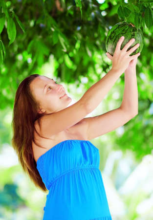 Young woman getting watermelon from the tree. Stock Photo - 15425725