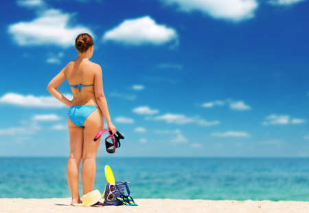 swimwear: Young woman on the beach. Water sport. Shallow DOF. Stock Photo