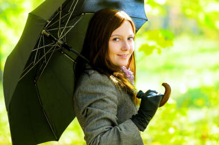 Young woman with umbrella in spring garden. photo