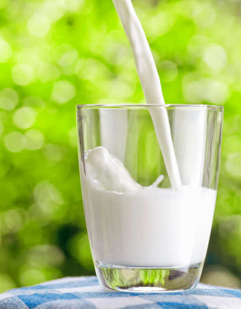 Glass of milk on nature background photo