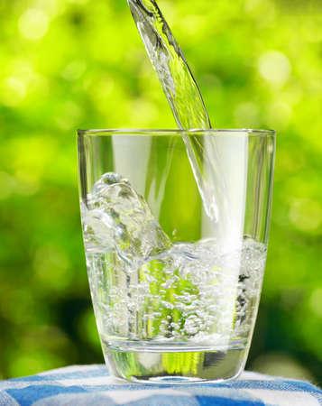 Szklanka wody na tle przyrody.