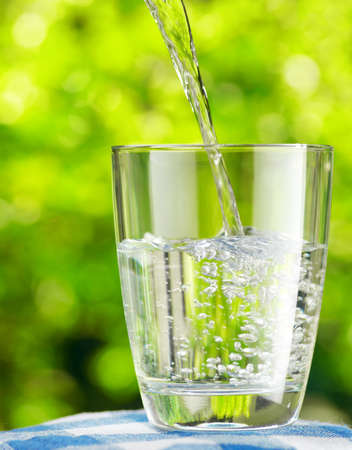 field glass: Glass of water on nature background.